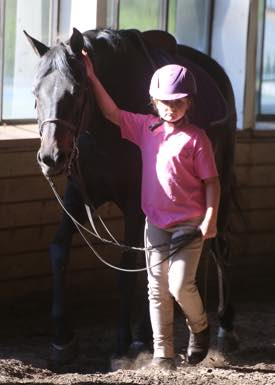 a young student cooling out her horse after her riding lesson