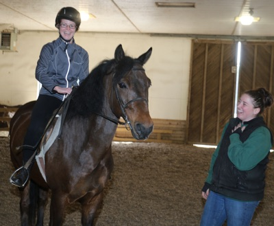 student in riding lesson and with her riding instructor